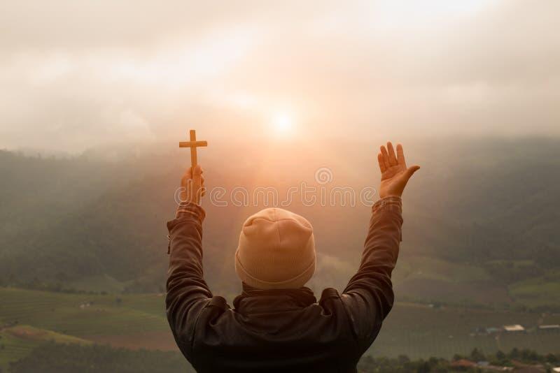 La mano humana lleva a cabo la cruz y la palma abierta para arriba adora Eucaristía Thera foto de archivo