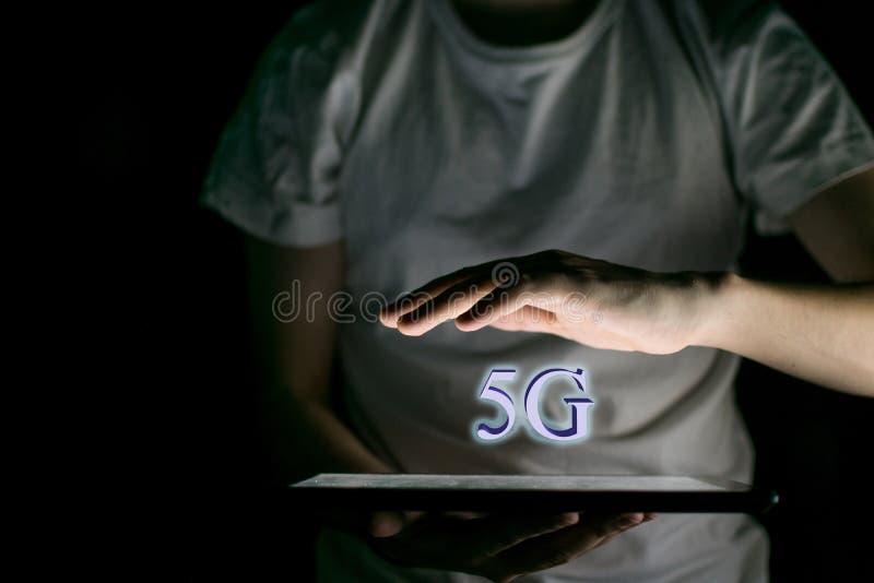 La mano iluminó por la luz de una tableta, Internet 5G imagen de archivo libre de regalías