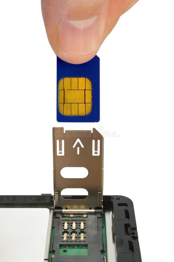 La mano instala la tarjeta del sim imagen de archivo libre de regalías