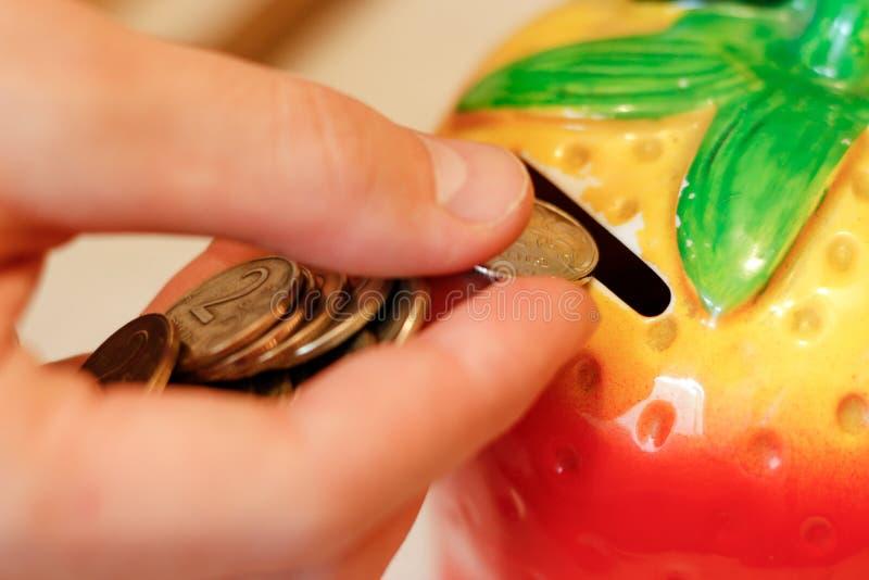 La mano lanza la moneda en el moneybox bajo la forma de strawber imagen de archivo libre de regalías