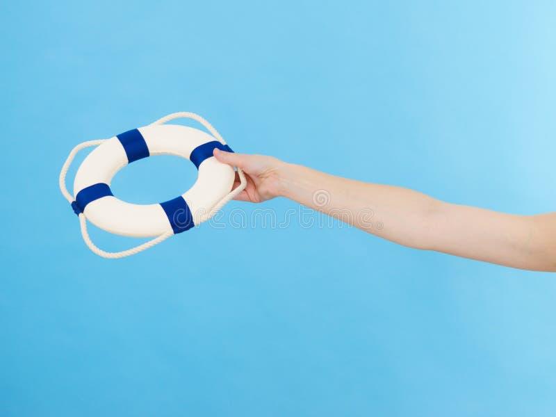 La mano lleva a cabo el anillo del rescate de la boya de vida imagen de archivo