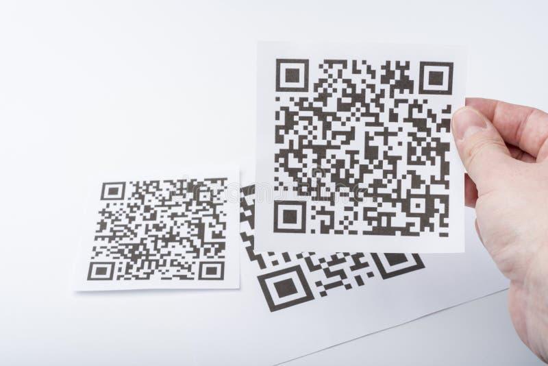 La mano lleva a cabo el código de transacción en un trozo de papel fotografía de archivo