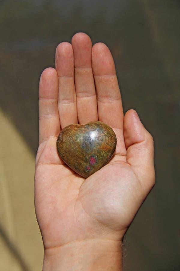 La mano lleva a cabo el corazón de la piedra natural del iotsit Corazón a disposición Una piedra en la forma de un corazón Talism imagen de archivo libre de regalías