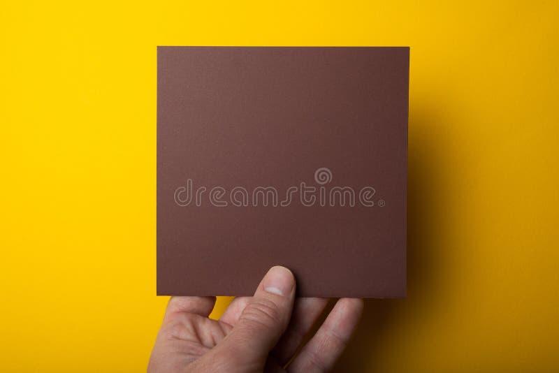 La mano lleva a cabo una disposición marrón cuadrada en un fondo amarillo Maqueta vac?a foto de archivo