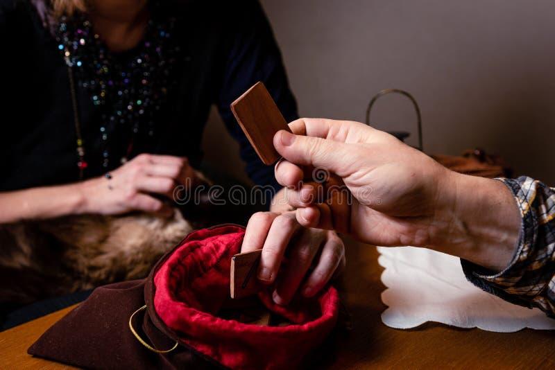 La mano maschile tiene una runa divinazione fotografie stock
