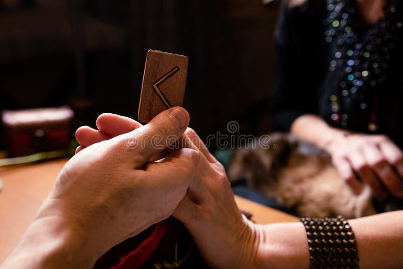 La mano maschile tiene una runa Kano significa 'fuoco' divinazione immagini stock libere da diritti