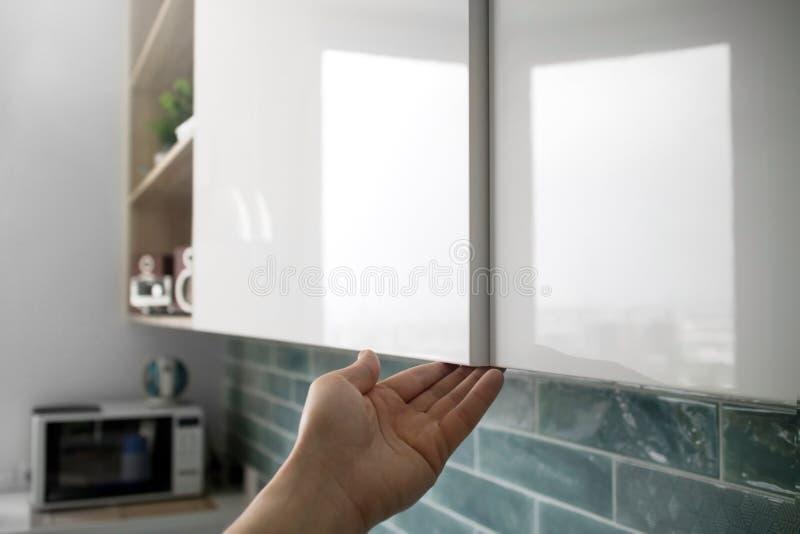 La mano maschio apre le porte dell'armadietto nella cucina immagini stock libere da diritti