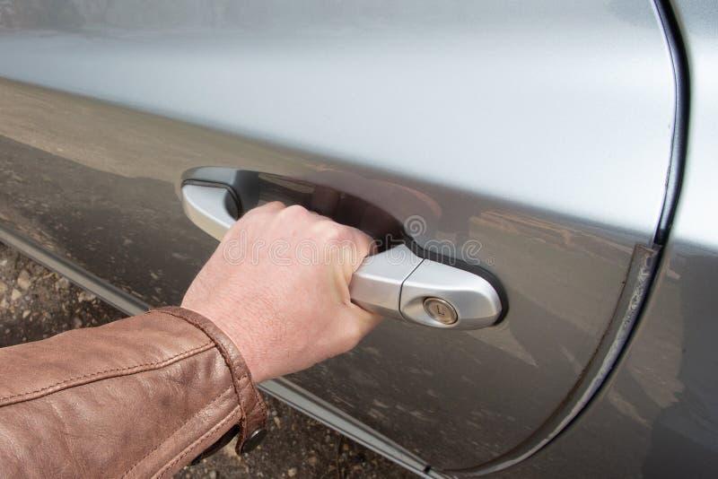 La mano maschio apre la porta di automobile con la maniglia interna immagine stock libera da diritti