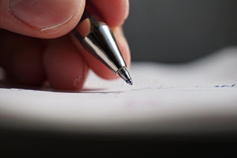 La mano maschio che tiene una penna blu dell 39 ufficio e che for Ufficio bianco e blu