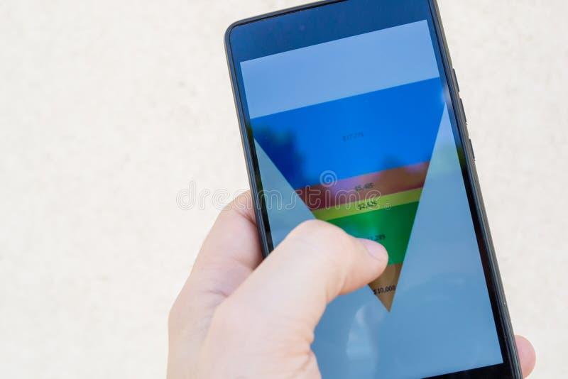 La mano maschio che tiene uno Smart Phone con le vendite versa il grafico con un imbuto fotografia stock libera da diritti