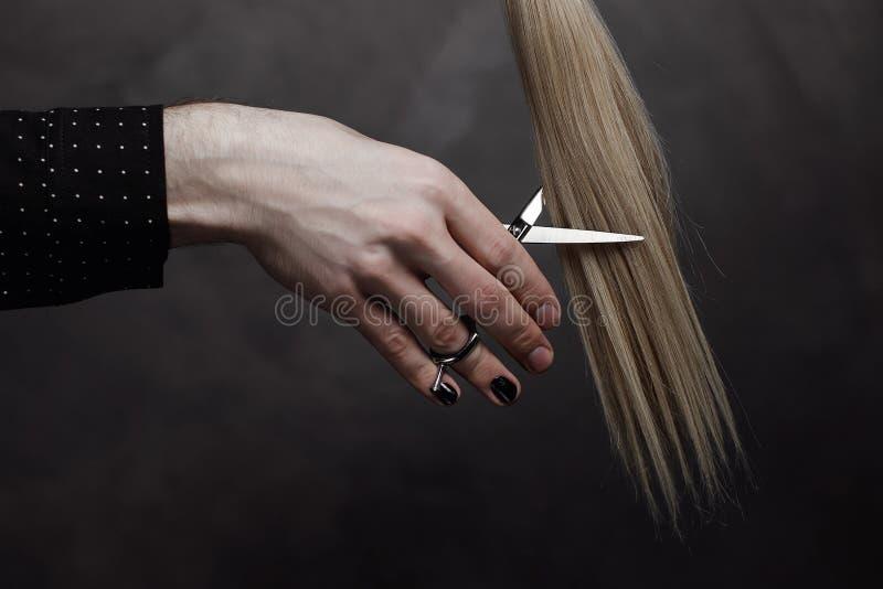 La mano maschio con il manicure tiene le forbici e una serratura di capelli immagini stock