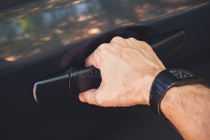 La mano maschio con l'orologio apre la porta di automobile fotografie stock