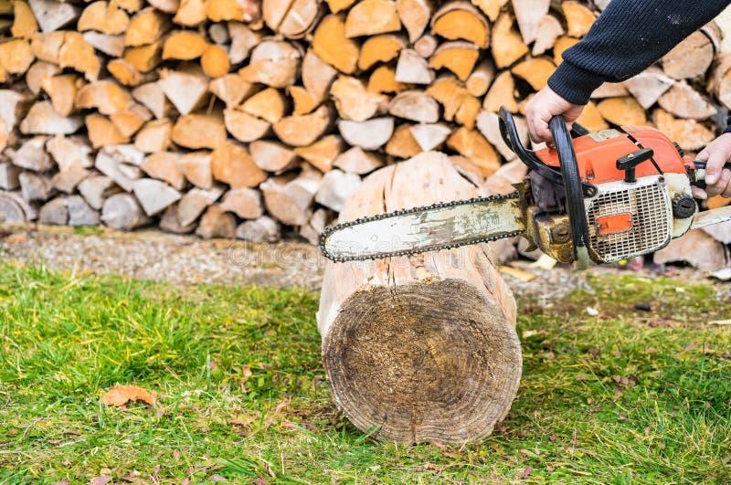 La mano maschio con la motosega sta tagliando la legna da ardere fotografie stock