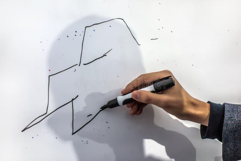La mano maschio con un indicatore disegna le linee fotografia stock libera da diritti