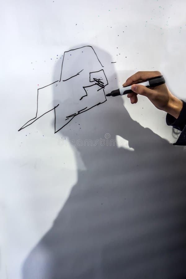 La mano maschio con un indicatore disegna le linee fotografie stock