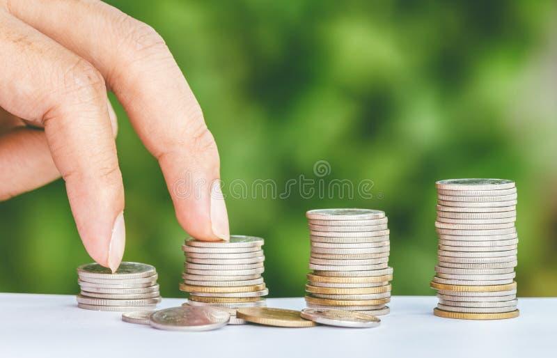 La mano maschio fa un passo sulla moneta dei soldi come l'affare crescente della pila immagini stock libere da diritti