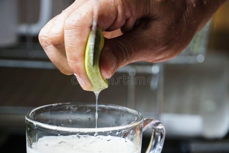 La mano maschio ha messo la calce in bevanda del latte di soia immagini stock