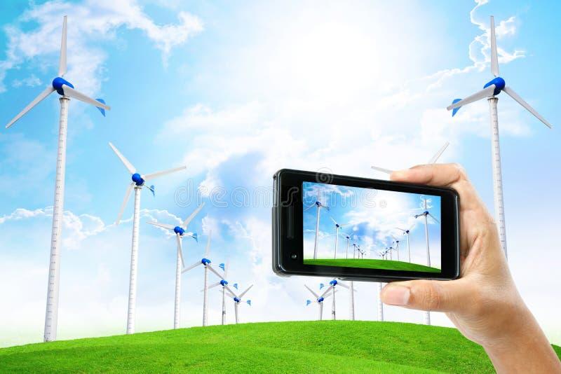 La mano maschio prende una foto dal telefono con il generatore eolico per l'industria e immagine stock libera da diritti