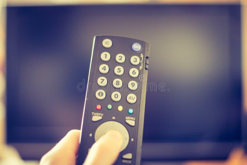 La mano maschio sta giudicando la TV TV telecomandata e astuta immagini stock