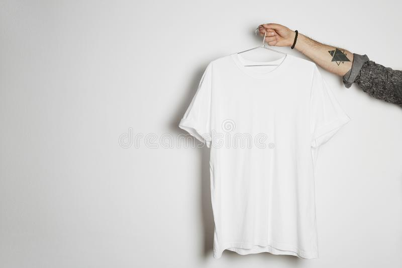 La mano maschio tatuata tiene la caduta con la maglietta bianca in bianco dal premio leggermente capisce il fondo bianco Pasta de fotografia stock libera da diritti