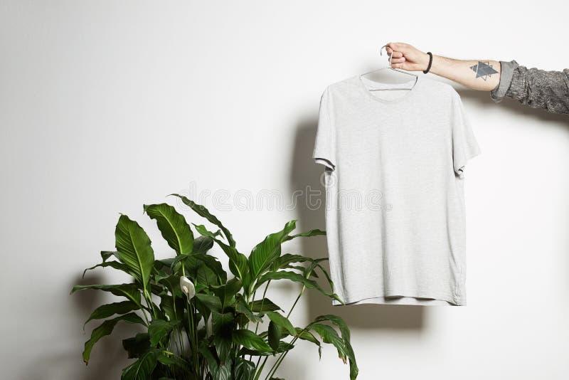 La mano maschio tatuata tiene l'attaccatura con la maglietta bianca in bianco dal premio leggermente capisce il fondo bianco Copi fotografia stock libera da diritti