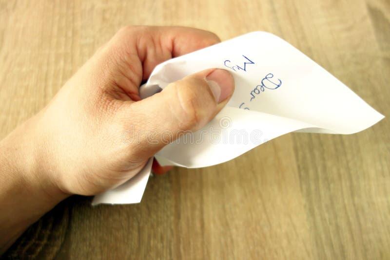 La mano masculina arruga el documento o la letra sobre fondo del escritorio de oficina imágenes de archivo libres de regalías
