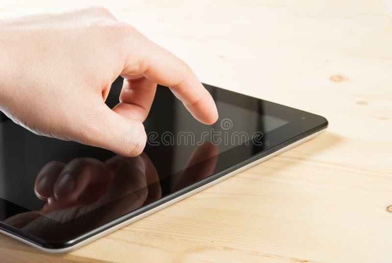 La mano masculina es PC digital conmovedora de la tableta en la tabla de madera foto de archivo libre de regalías