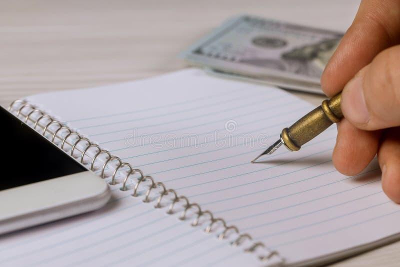 La mano masculina escribe a pluma en libreta los d?lares, smartphone fotos de archivo libres de regalías