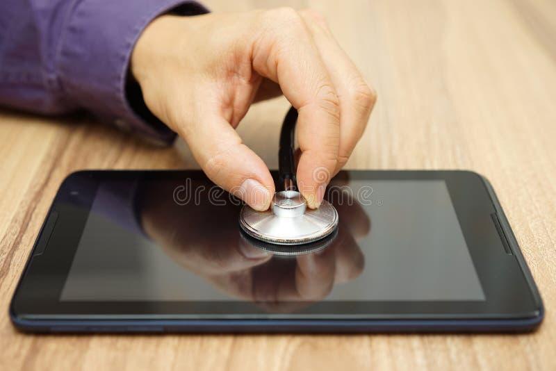 La mano masculina está sosteniendo un estetoscopio sobre la tableta, repai fotografía de archivo libre de regalías