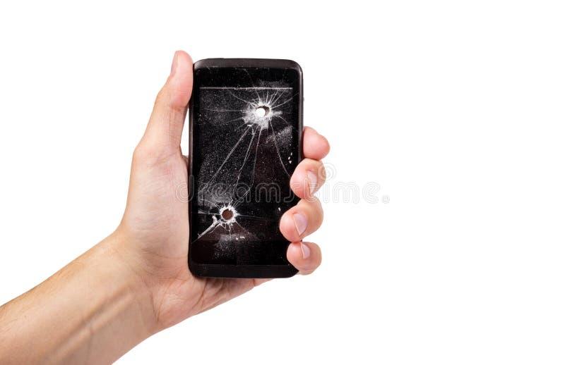 La mano masculina está sosteniendo un teléfono móvil quebrado Teléfono elegante con el agujero de bala fotos de archivo