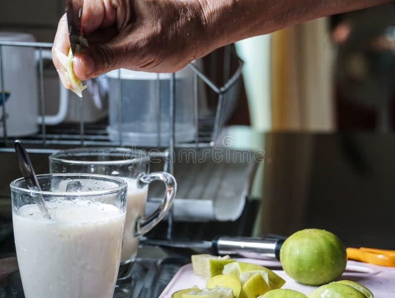 La mano masculina puso la cal en bebida de la leche de soja imagen de archivo libre de regalías