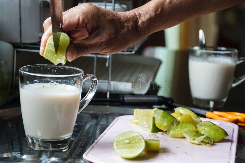La mano masculina puso la cal en bebida de la leche de soja imagen de archivo