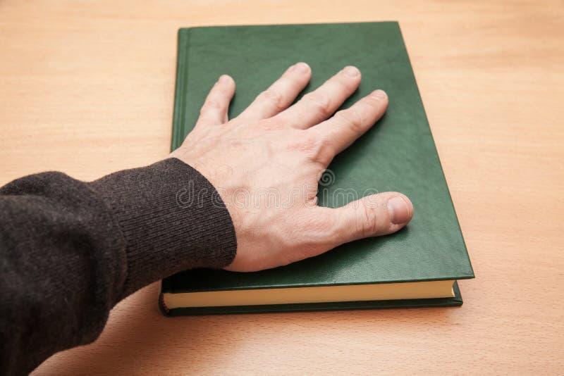 La mano masculina que pone en el libro, jura concepto fotos de archivo