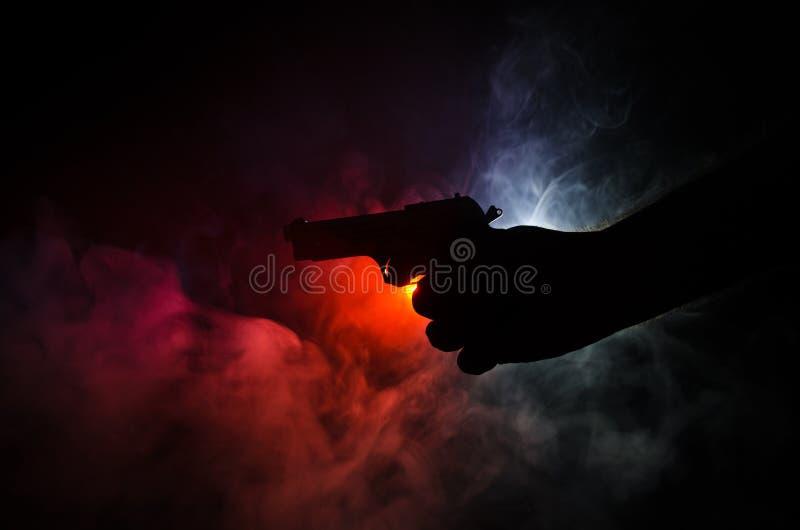 La mano masculina que sostenía el arma en fondo negro con el humo (blanco rojo amarillo-naranja) coloreó las luces traseras, conc imagen de archivo