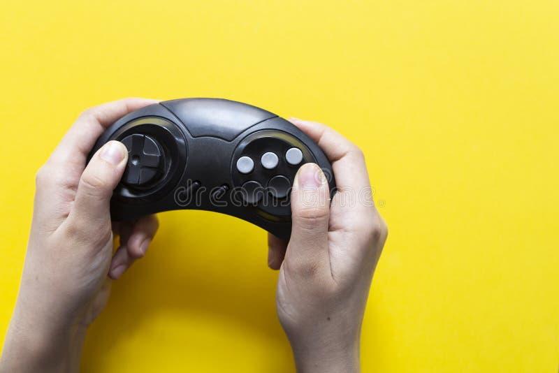 La mano masculina sostiene una palanca de mando para los videojuegos en un fondo amarillo Gamepad en sirve la mano en un fondo am imagenes de archivo