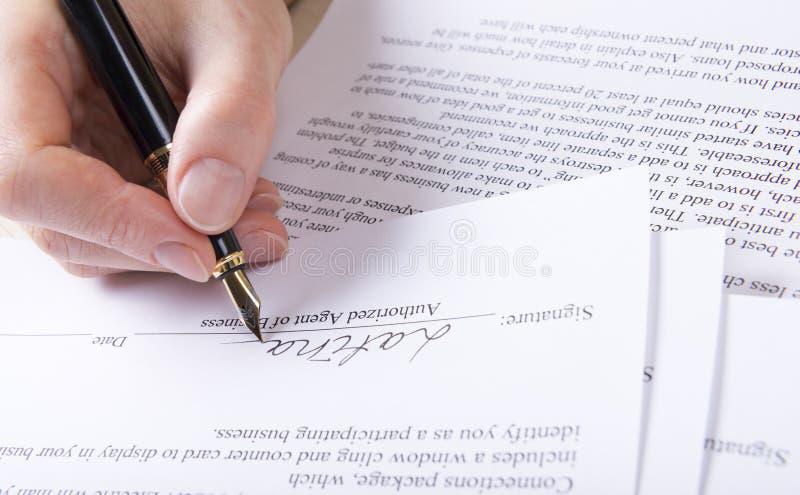 La mano mette la firma nel contratto immagine stock libera da diritti