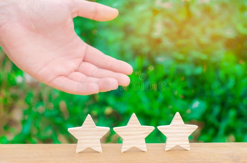 La mano mostra ai tre lo stasr Il concetto di riconoscimento di alta qualità e di buon servizio Hotel o caffè di rassegna Alta va immagini stock libere da diritti