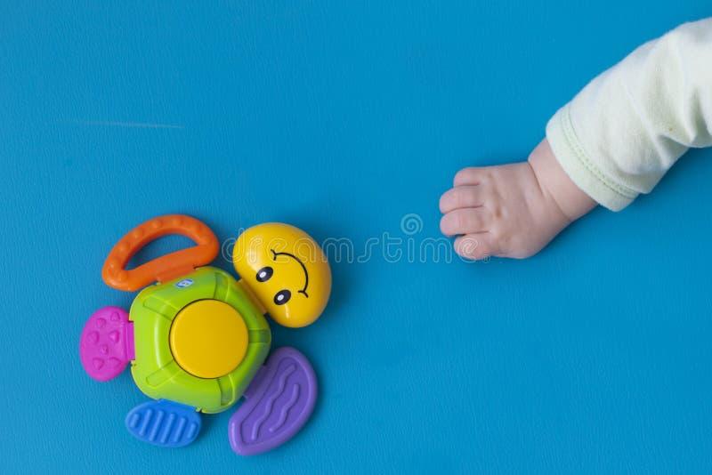 La mano neonata del bambino allunga alla destra al giocattolo di una di una tartaruga colorata multi con un sorriso su un fondo b immagini stock