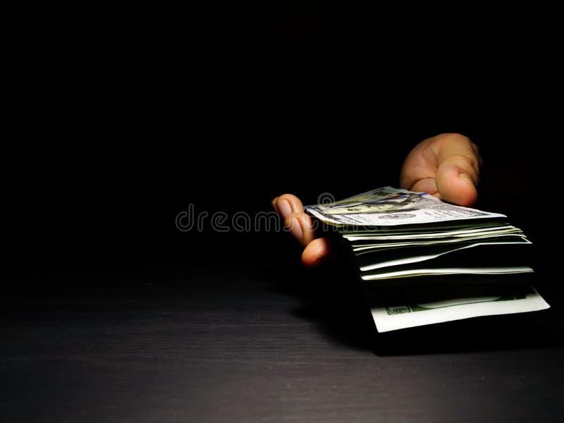 La mano ofrece billetes de banco del dólar con el espacio libre Dinero para prestar imagenes de archivo
