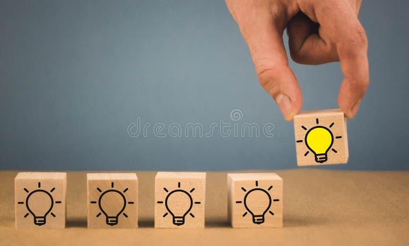 la mano opera una scelta e sceglie una lampadina bruciante, un simbolo di un'idea originale fotografia stock libera da diritti