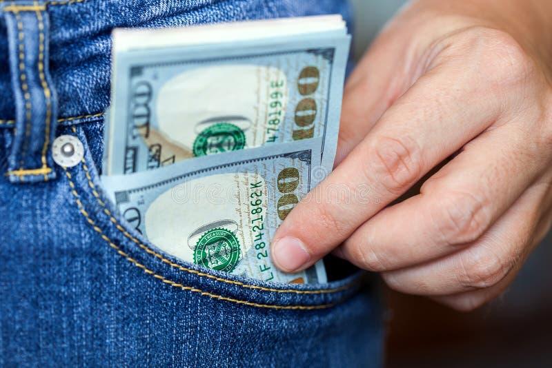 La mano ottiene i dollari da una tasca fotografia stock