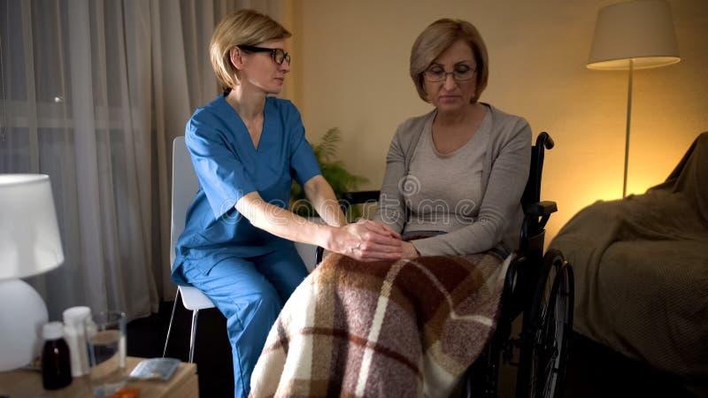 La mano paziente di signora della tenuta dell'infermiere prova a confortare il supporto di servizio medico, si preoccupa fotografia stock