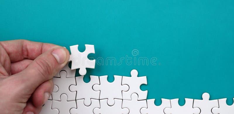 La mano piega un puzzle bianco contro lo sfondo della superficie blu Foto di struttura con spazio per testo immagini stock