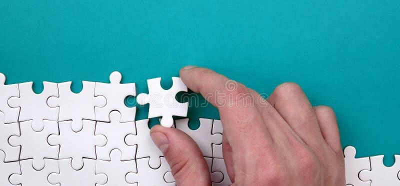 La mano piega un puzzle bianco contro lo sfondo della superficie blu Foto di struttura con spazio per testo fotografie stock