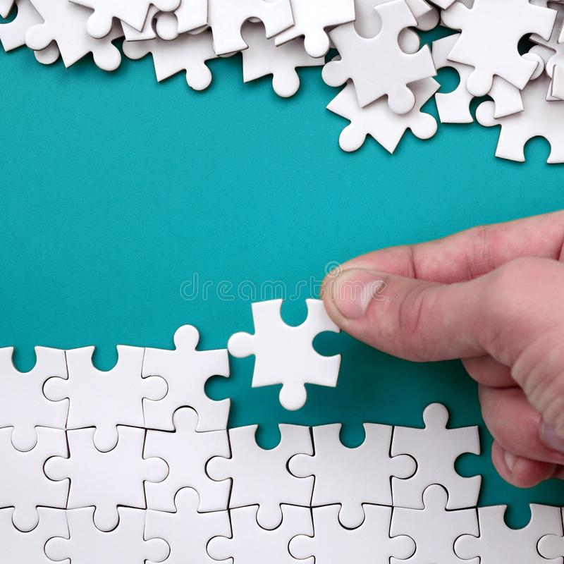 La mano piega un puzzle bianco e un mucchio dei pezzi spettinati di puzzle si trova contro lo sfondo della superficie blu Struttu fotografia stock libera da diritti