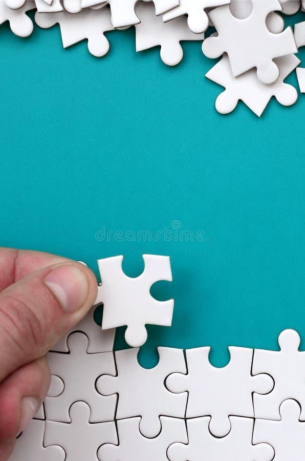 La mano piega un puzzle bianco e un mucchio dei pezzi spettinati di puzzle si trova contro lo sfondo della superficie blu Struttu fotografie stock