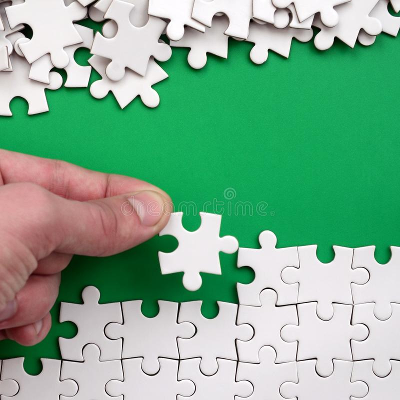 La mano piega un puzzle bianco e un mucchio dei pezzi spettinati di puzzle si trova contro lo sfondo della superficie verde Textu fotografia stock libera da diritti