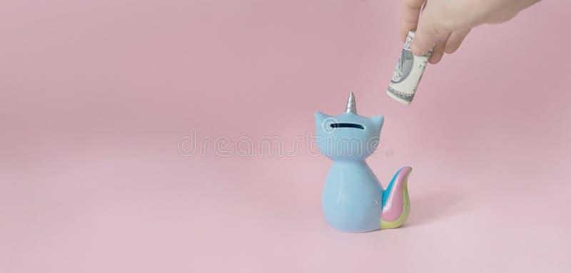 La mano pone un dólar en el azul del maíz de la hucha del gatito con una cola del arco iris y un cuerno coloridos del unicornio e fotografía de archivo libre de regalías