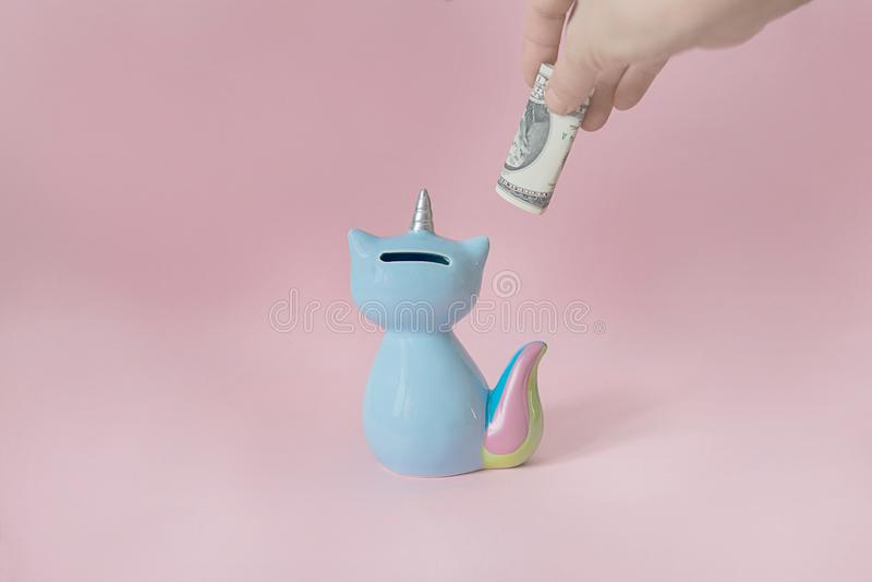 La mano pone un dólar en el azul del maíz del gatito del moneybox con una cola colorida del arco iris con ojos cerrados y un cuer imagen de archivo