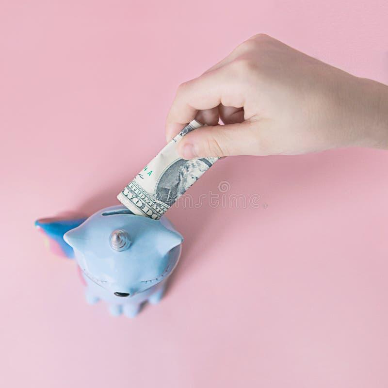 La mano pone un dólar en el azul del maíz del gatito del moneybox con una cola colorida del arco iris con ojos cerrados y un cuer imagenes de archivo
